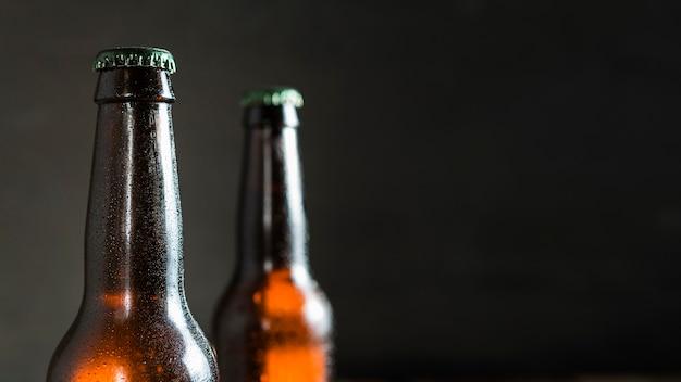 Vista frontale delle bottiglie di vetro di birra con lo spazio della copia