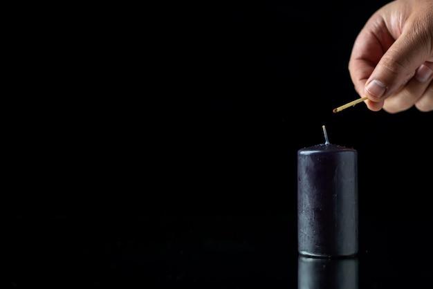 Vista frontale della candela nera che ottiene luce dal maschio sulla superficie scura