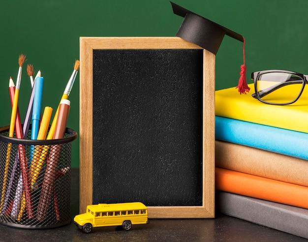 Vista frontale della lavagna con cappuccio accademico e pila di libri