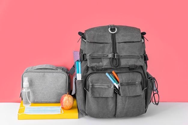 Vista frontale della borsa del libro per tornare a scuola con mela e maschera