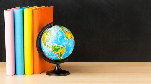 Vista frontale di libri per tornare a scuola con il globo