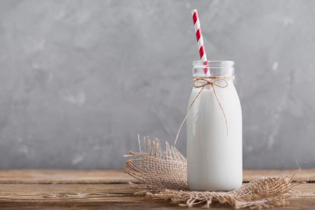 Vista frontale bottiglia di latte con paglia