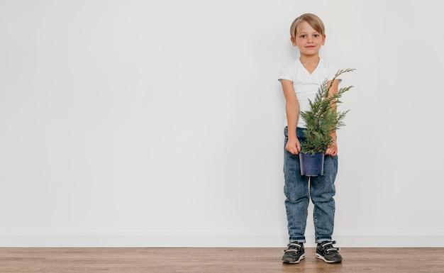 Vista frontale del ragazzo che tiene il vaso della pianta con lo spazio della copia