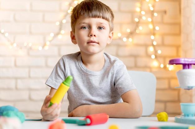 Ragazzo di vista frontale che gioca con i giocattoli
