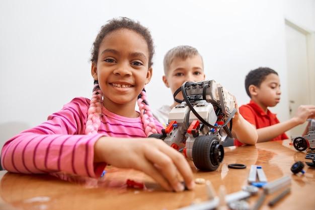 Vista frontale del kit di costruzione per un gruppo di tre bambini multirazziali che creano giocattoli