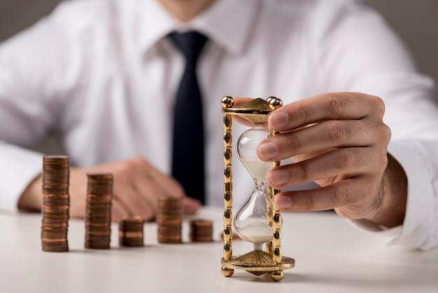 Vista frontale della clessidra della tenuta dell'uomo di affari con le monete