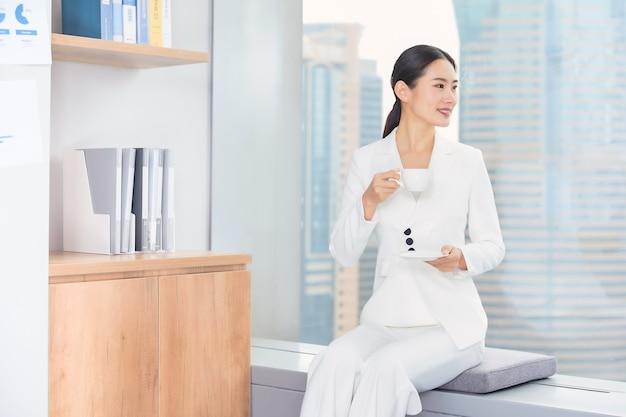 Vista frontale della donna di affari che tiene caffè