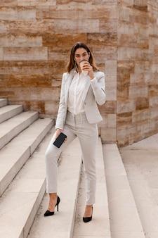 Vista frontale della donna di affari con smartphone che beve caffè