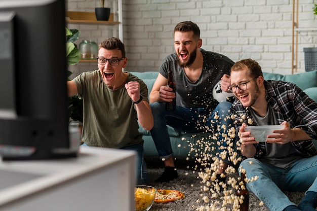Vista frontale di allegri amici maschi che guardano insieme sport in tv mentre mangiano spuntini