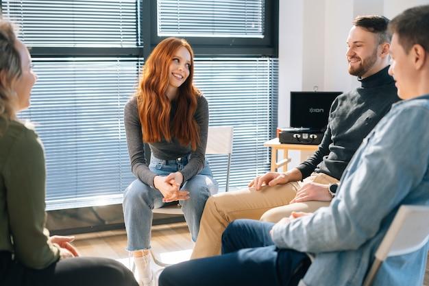 Vista frontale di allegra giovane donna d'affari rossa che parla e discute di nuove idee con un team di business creativo, durante il brainstorming di progetti di avvio nella moderna stanza dell'ufficio vicino alla finestra.