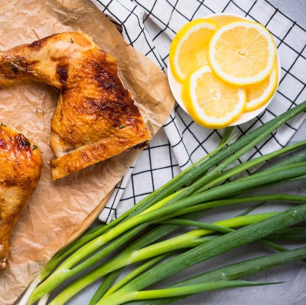 Cosce di pollo vista frontale con fette di limone