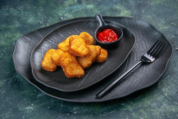 Vista frontale delle pepite di pollo e della forchetta del ketchup in lastre nere su superficie scura dark