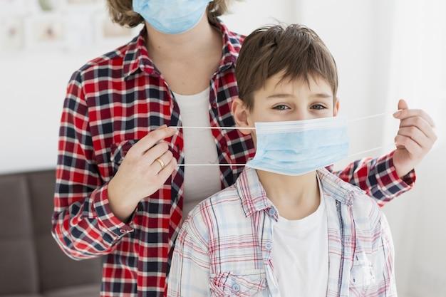Vista frontale del bambino aiutato dalla madre a indossare la maschera medica