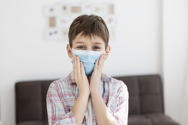 Vista frontale del bambino che posa mentre indossa maschera medica