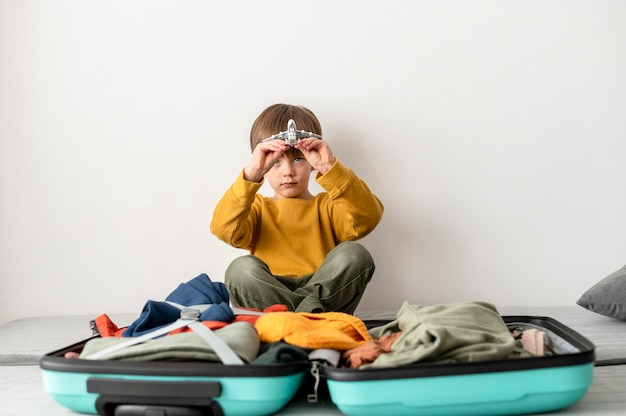 Vista frontale del bambino seduto accanto al bagaglio a casa e tenendo la figurina dell'aeroplano