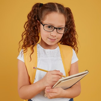Bambino di vista frontale che scrive e che guarda l'obbiettivo