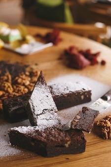 Una barretta di cioccolato di vista frontale con noci sul pavimento di legno marrone