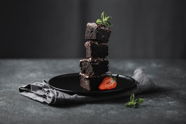 Vista frontale dei pezzi di torta al cioccolato sulla piastra con la menta