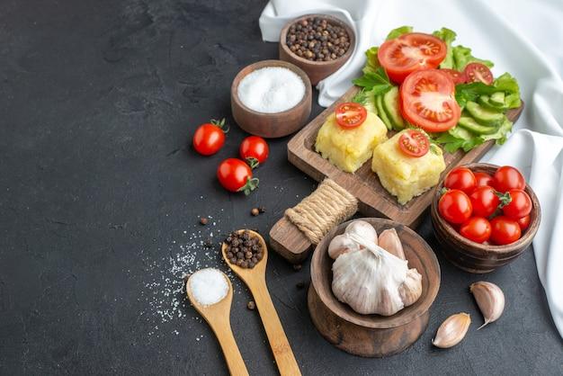Vista frontale di verdure fresche tritate e intere sul tagliere in ciotole e spezie su asciugamano bianco su superficie nera