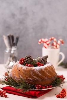 Vista frontale della torta di natale con pigne e bacche rosse