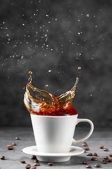 Vista frontale del caffè che spruzza in tazza