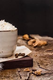 Vista frontale caffè con latte e panna montata con biscotto