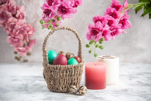 Vista frontale uova di pasqua colorate all'interno del cesto progettato con fiori e candele su superficie bianca