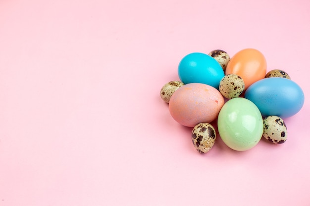 Vista frontale uova di pasqua colorate su superficie rosa colorato colore primaverile vacanze pasqua concetto ornato