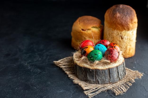 Vista frontale uova di pasqua colorate su un pezzo di legno sfondo scuro colore etnico ornato colorato holiday