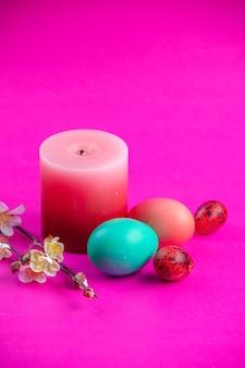 Vista frontale uova dipinte colorate con candela su sfondo rosa concetto di primavera vacanza etnico ornato colorato