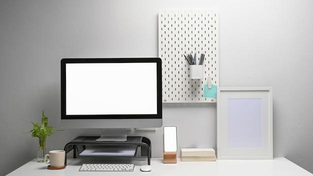 Vista frontale del computer con schermo vuoto, smartphone e forniture per ufficio sul posto di lavoro contemporaneo.