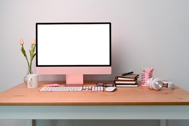 Computer vista frontale con forniture pubblicitarie schermo bianco sulla scrivania in legno.