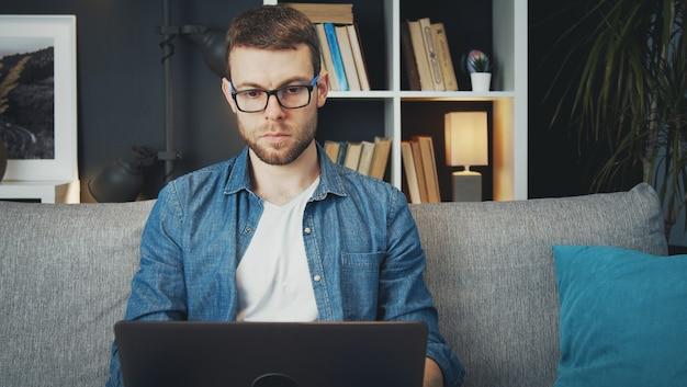 Vista frontale dell'uomo concentrato utilizzando laptop seduto sul divano a lavorare da casa durante il blocco