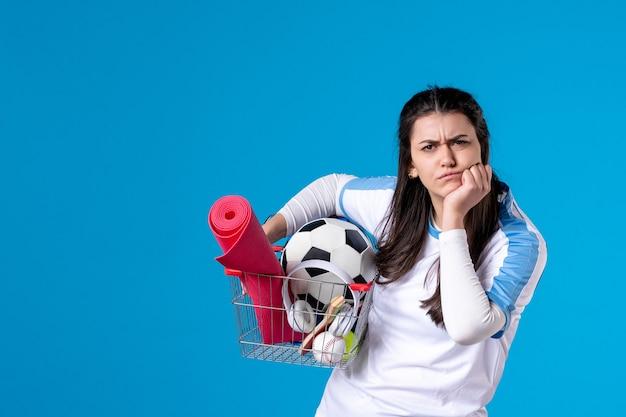 Vista frontale concentrata giovane femmina con cestino dopo lo shopping sportivo