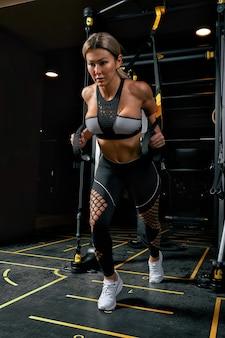Vista frontale della giovane donna bionda fiduciosa facendo allenamento di sollevamento pesi attraente giovane donna sollevamento pesi guardando in avanti forte forma del corpo addestrato braccia braccia gambe.