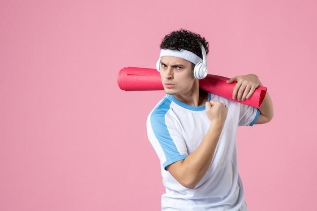 Vista frontale fiducioso giovane maschio in abiti sportivi con materassino yoga