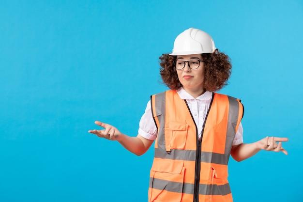 Vista frontale del costruttore femminile confuso in uniforme sulla parete blu