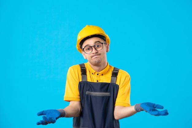 Vista frontale del costruttore maschio confuso in uniforme e guanti sulla superficie blu