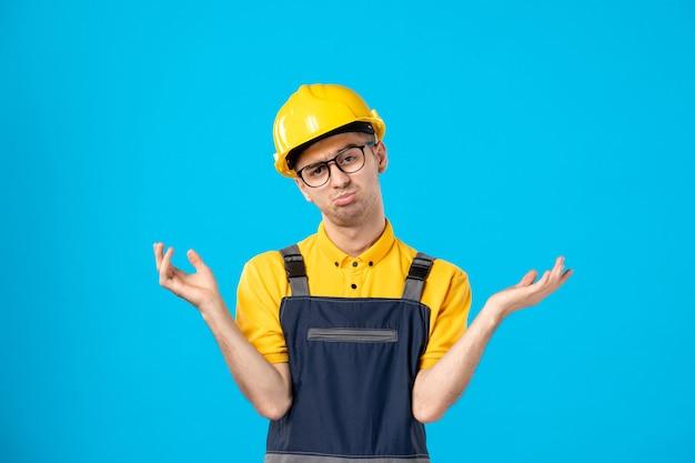 Operaio maschio confuso vista frontale in uniforme gialla sull'azzurro