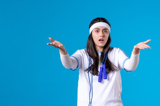 Vista frontale donna graziosa confusa in abiti sportivi con corda per saltare