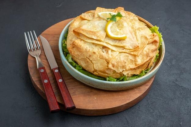 Vista frontale pita cotta all'interno del piatto con verdure e fette di limone sulla superficie scura