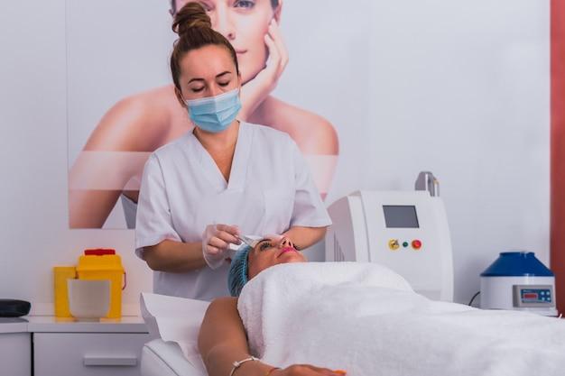 Vista frontale di un cosmetologo che fa un trattamento di bellezza applicando vitamine e maschera d'oro al viso di una donna adulta per il ringiovanimento nel centro termale.