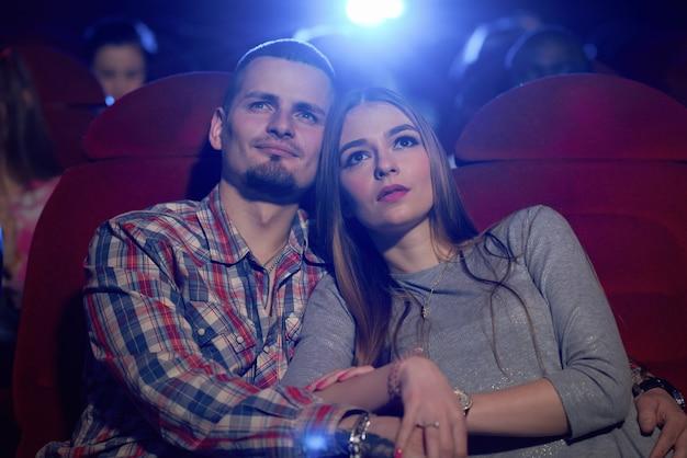 Vista frontale della coppia seduta insieme al cinema, guardare commedia o film romantico. uomo barbuto bello che abbraccia bella ragazza che si siede vicino mentre rassegna di film. concetto di tempo libero.