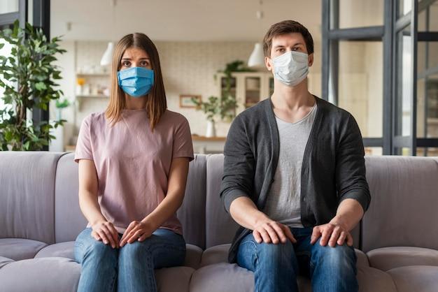 Vista frontale delle coppie facendo uso della maschera medica