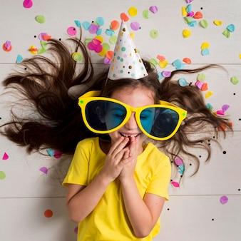 Vista frontale della bambina carina con grandi occhiali da sole e cappello da festa