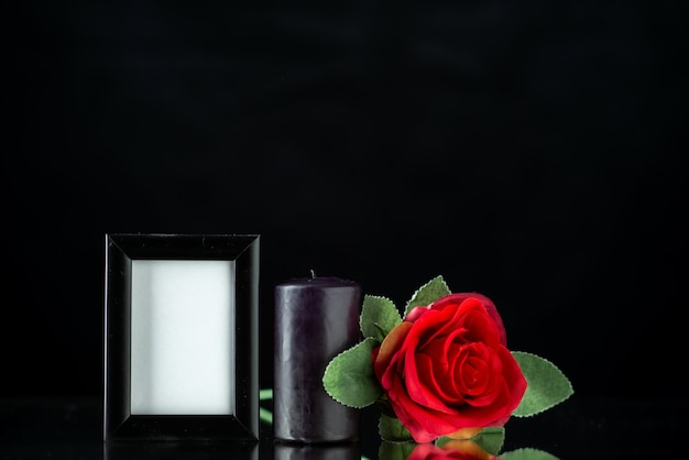 Vista frontale della candela scura con rosa rossa e cornice sulla superficie scura