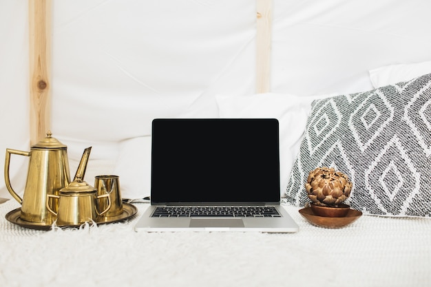 Vista frontale dell'area di lavoro della scrivania dell'ufficio domestico decorata con un computer portatile a schermo vuoto. concetto di business in stile moderno