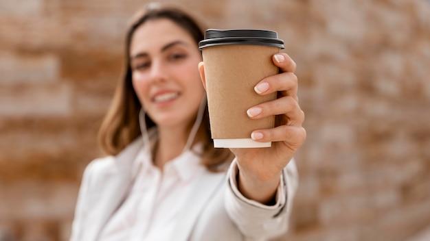 Vista frontale della donna di affari defocused con gli auricolari che mostrano la tazza di caffè