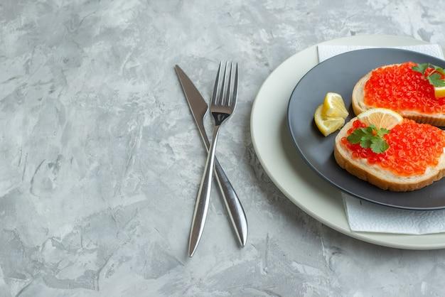 Vista frontale deliziosi panini al caviale all'interno della piastra sulla superficie bianca snack pane colazione cena cibo per pesci toast piatto