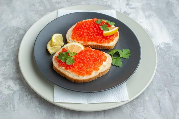 Vista frontale deliziosi panini al caviale all'interno della piastra sulla superficie bianca snack piatto di pane colazione pasto cena cibo per pesci toast